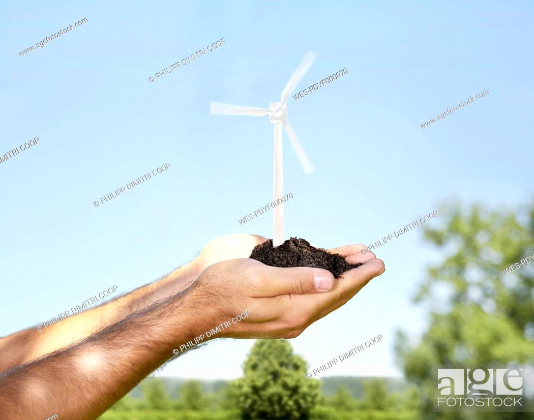 Stock Photo: Germany, Cologne, Young man holding wind turbine with soil.