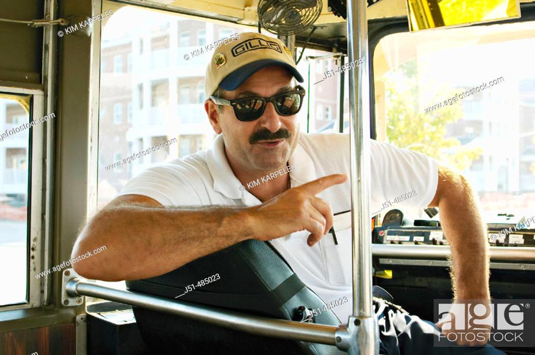 Stock Photo: WISCONSIN. Kenosha. Restored streetcar, driver wearing baseball cap, turned around in seat, windshield.