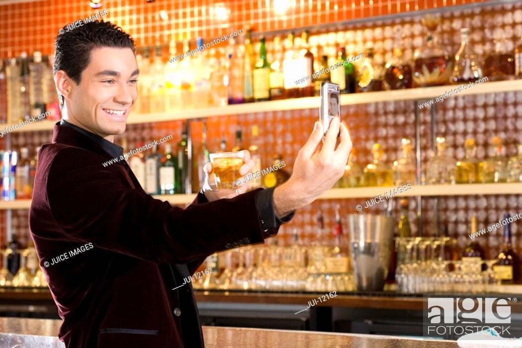 Stock Photo: Young man by bar with drink, taking photograph, smiling.