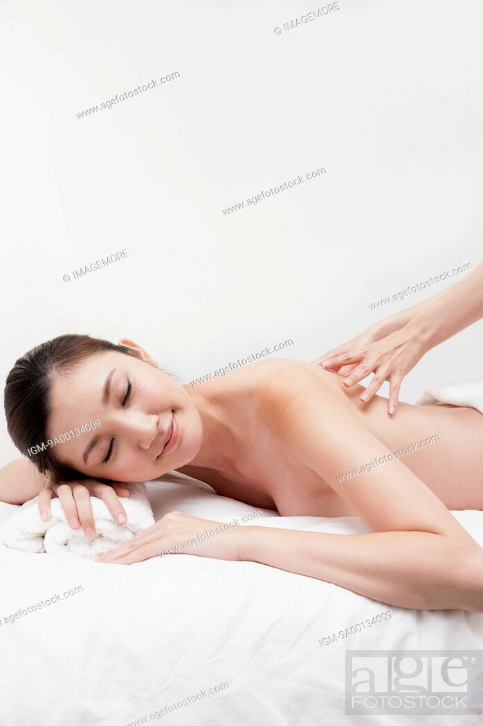 Imagen: Young woman lying down with eyes closed and massaging.