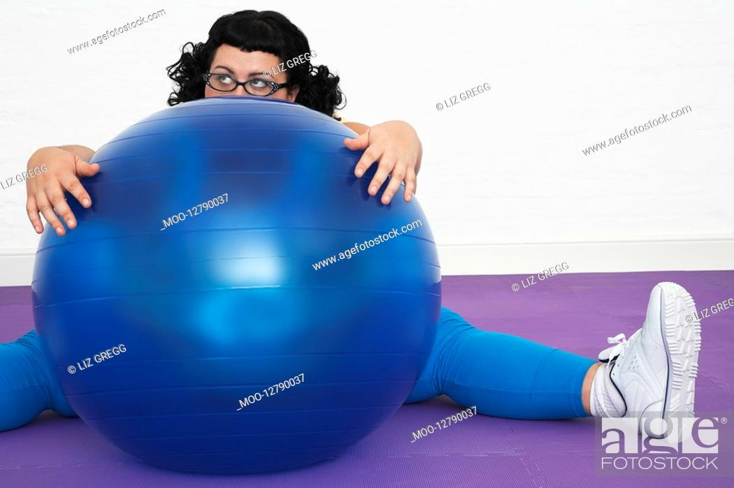 Stock Photo: Uninspired overweight Woman sitting Behind Exercise Ball.
