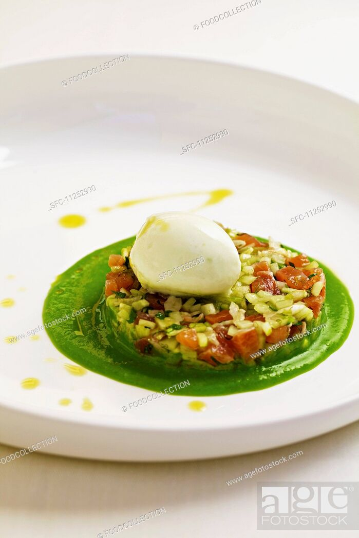 Stock Photo: Salmon trout tartar with fennel and cucumber served on a bed of young peas with lemon balm ice cream.