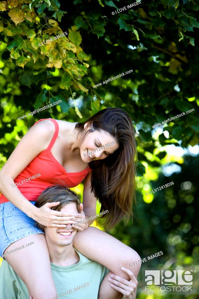 Stock Photo: A young man carrying his girlfriend on his shoulders.