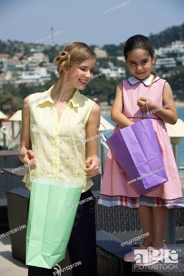 Imagen: Mother and daughter looking in shopping bags.