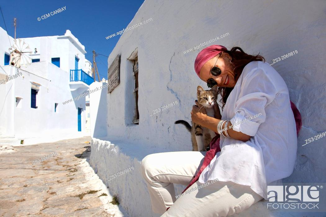 Stock Photo: Woman with a local cat, Amorgos, Cyclades Islands, Greek Islands, Greece, Europe.