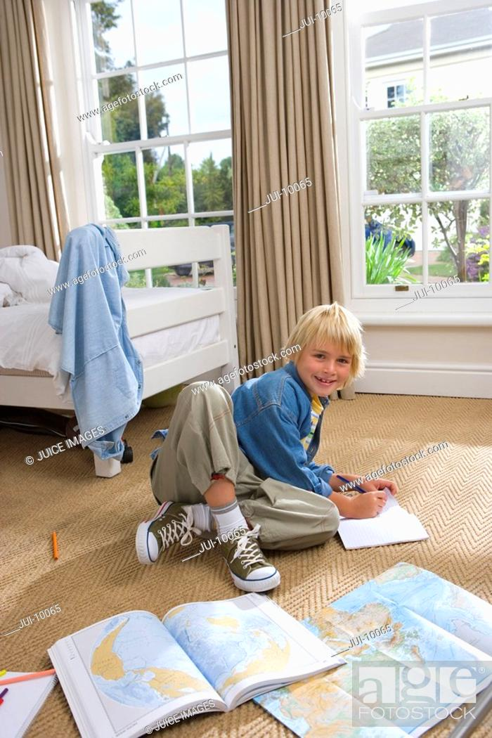Stock Photo: Boy 6-8 in bedroom drawing, smiling, portrait.