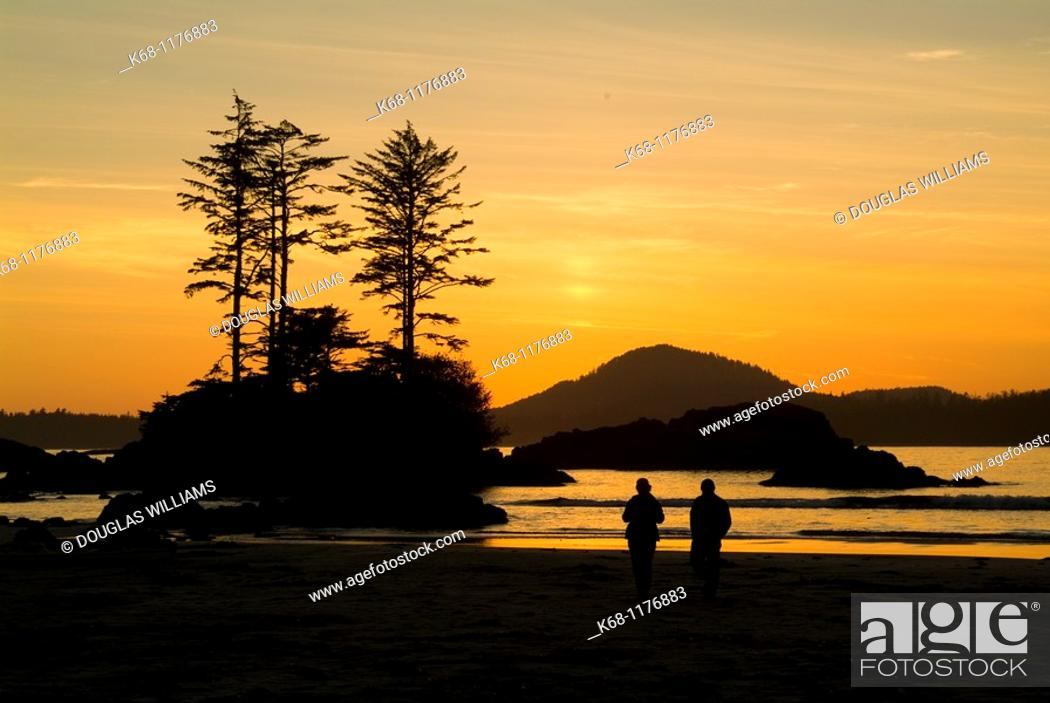 Stock Photo: couple walks on the beach on Flores Island, BC, at sunset.