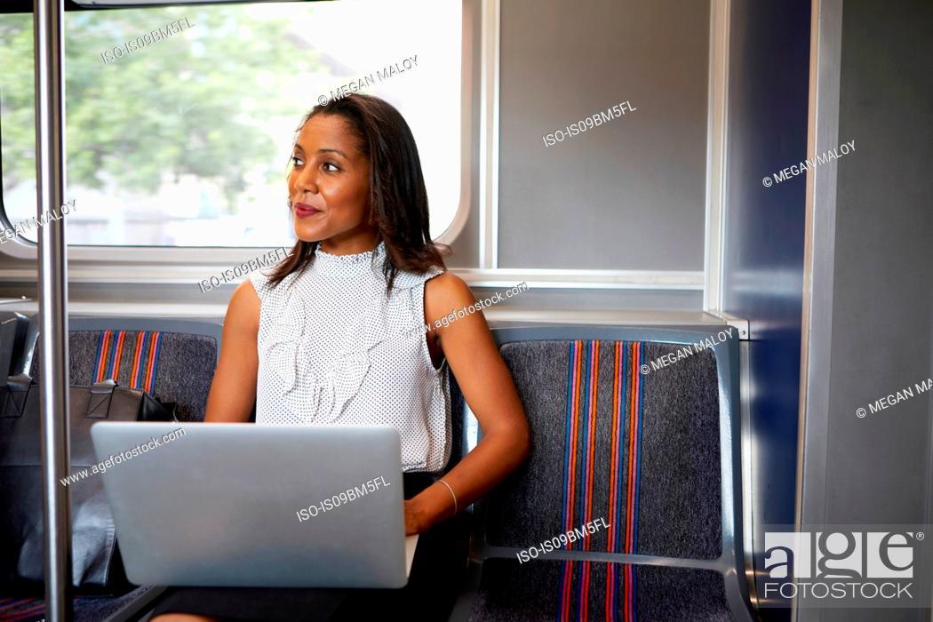Imagen: Businesswoman using laptop on train.