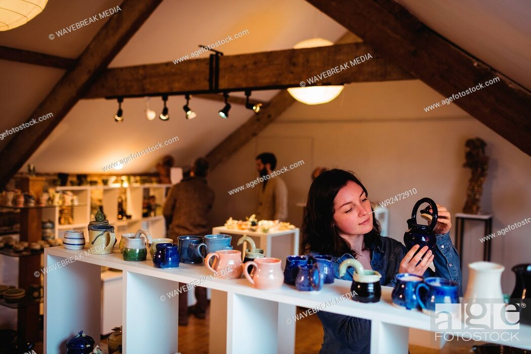 Stock Photo: Female customer holding container at pottery store.