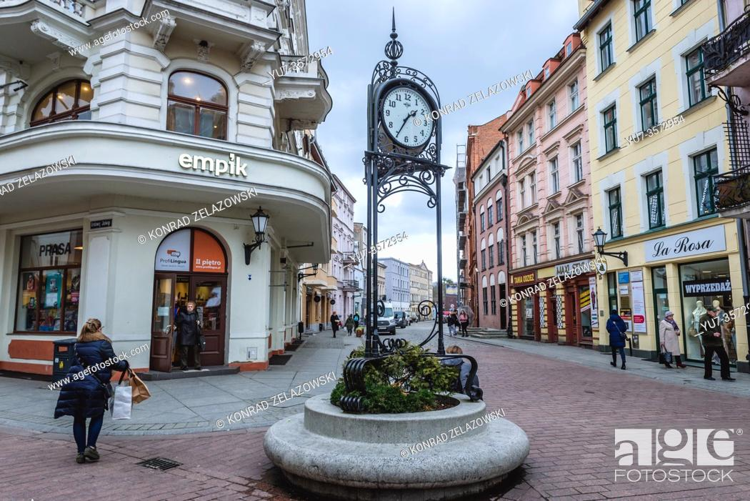 Stock Photo: A clock at intersection of Szeroka, Krolowej Jadwigi and Wielkie Garbary Streets in Old Town of Torun city, Kuyavian Pomeranian Voivodeship of Poland.