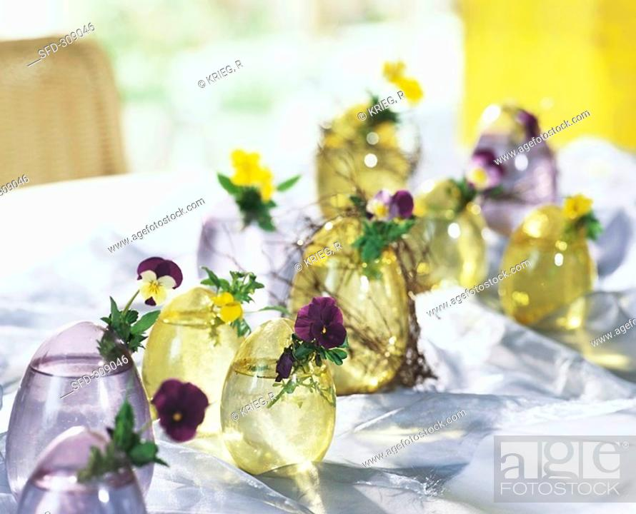 Stock Photo: Glass Easter egg vases with horned violets & pansies.