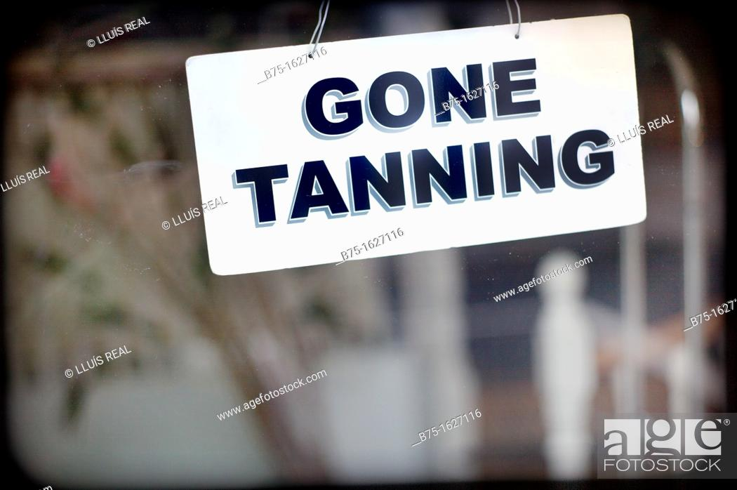 Stock Photo: closed sign in a business, gone tanning.