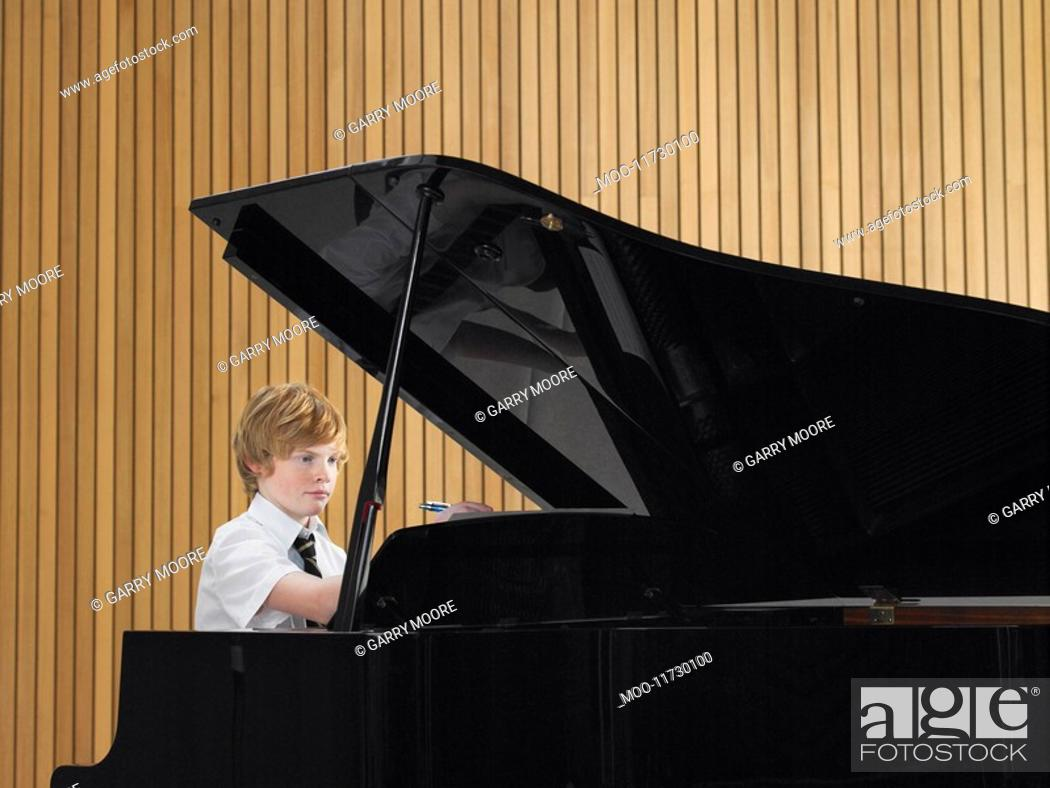 Stock Photo: Pre teen boy playing piano in music class.