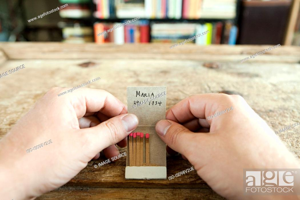 Stock Photo: Person holding matchbook with phone number written on it.