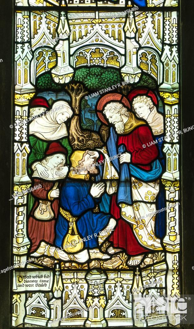 Stock Photo: Stained glass depicting St Paul healing the sick, St Mary's Priory Church, Abergavenny Wales UK. May 2019.