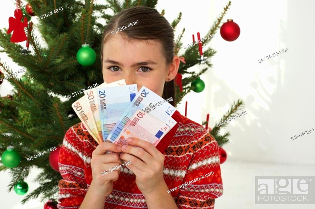 Stock Photo: Girl holding banknotes in front of a Christmas tree.