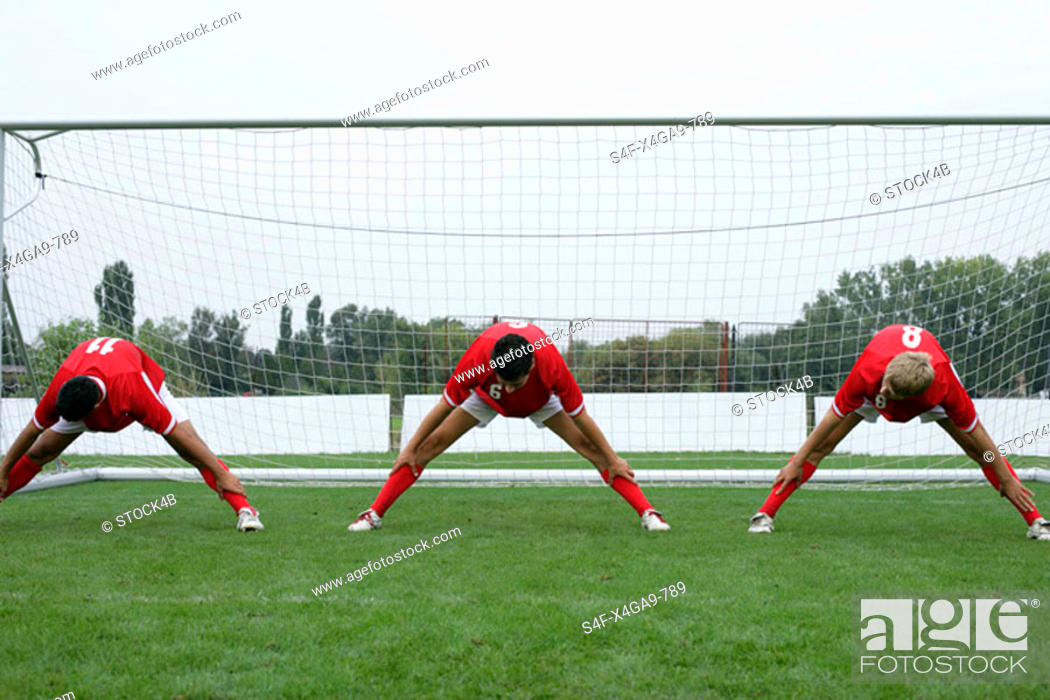 Stock Photo: Three soccer players doing stretching exercise in front of the goal.