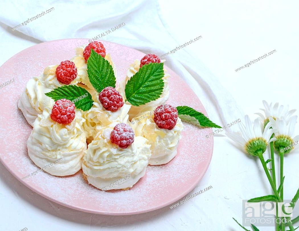 Stock Photo: baked cakes made of egg white and whipped white cream with raspberries on a pink plate, Pavlova dessert.