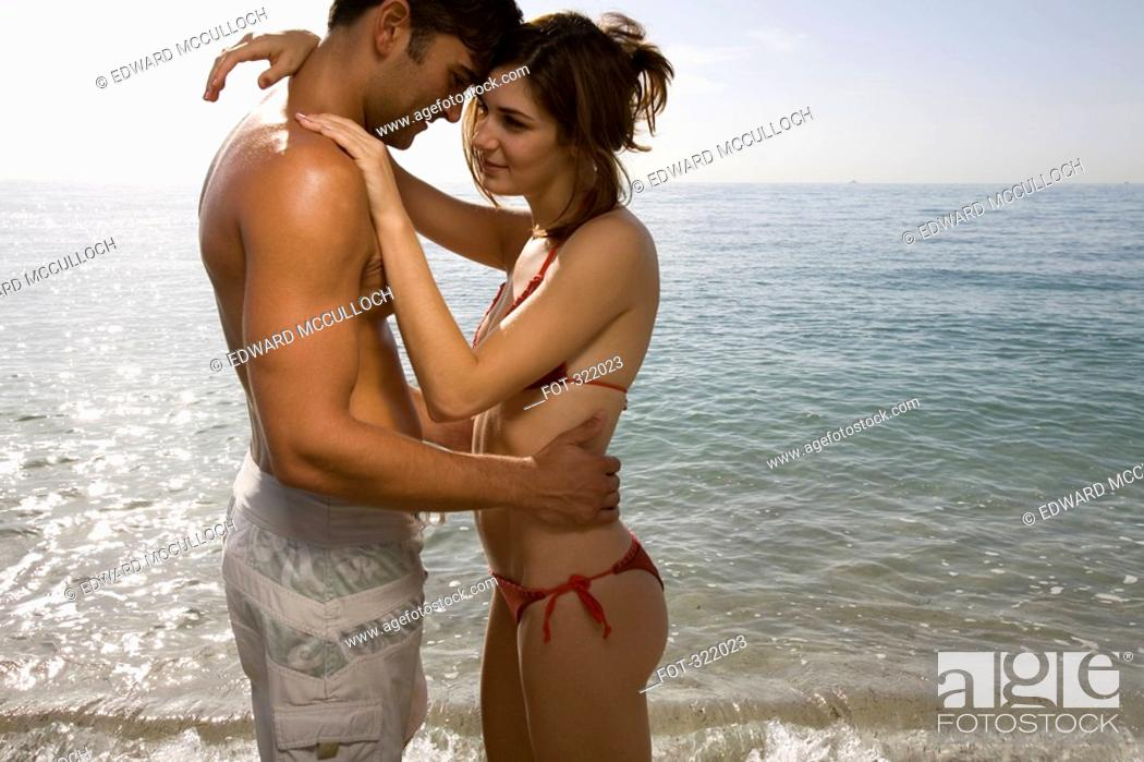 Stock Photo: Couple embracing in front of sea.