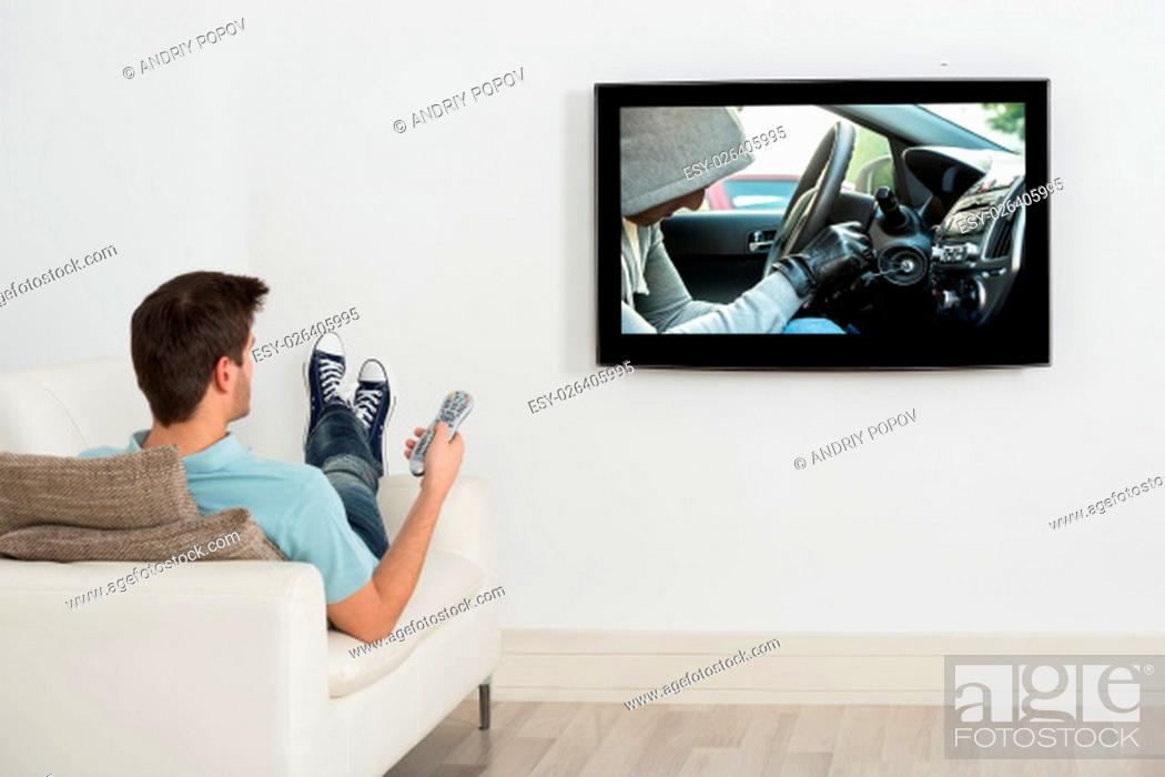Stock Photo: Young Man Lying On Couch Watching Movie On Television.