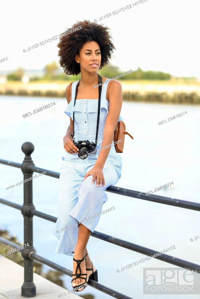 Stock Photo: Portrait of fashionable young woman with camera and backpack.