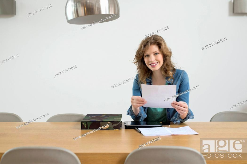 Stock Photo: Portrait of a woman sorting out bills.