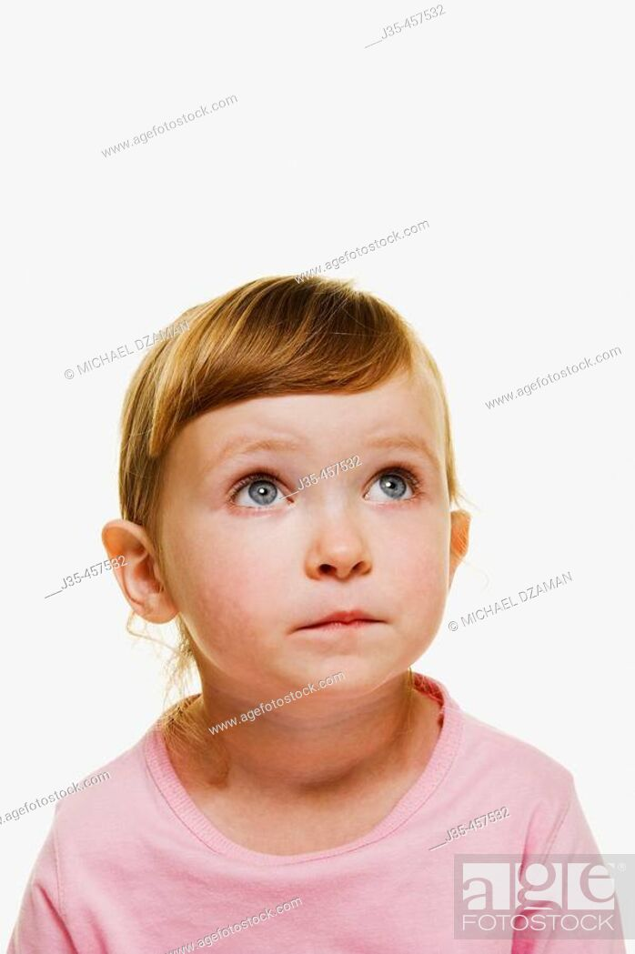 Stock Photo: A three year old girl with blonde hair wearing  a pink top and hair pulled back,  looks upwards.