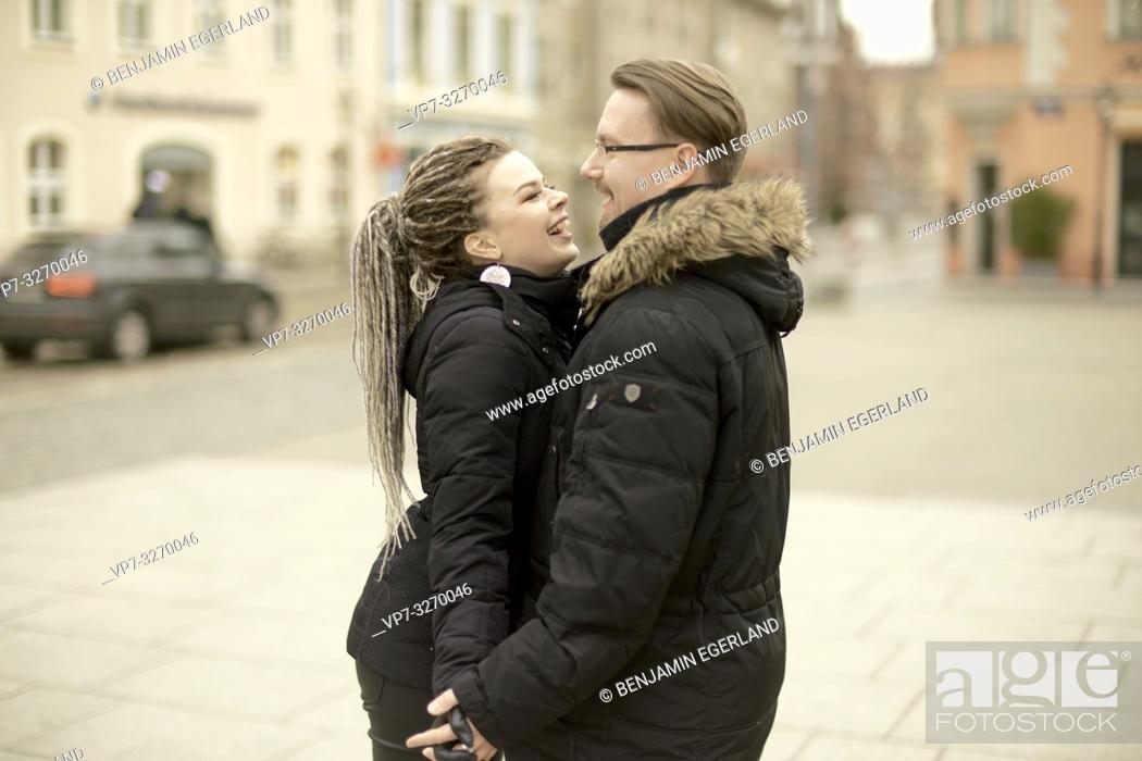 Stock Photo: happy couple in town, looking at each other, side view, in Cottbus, Brandenburg, Germany.