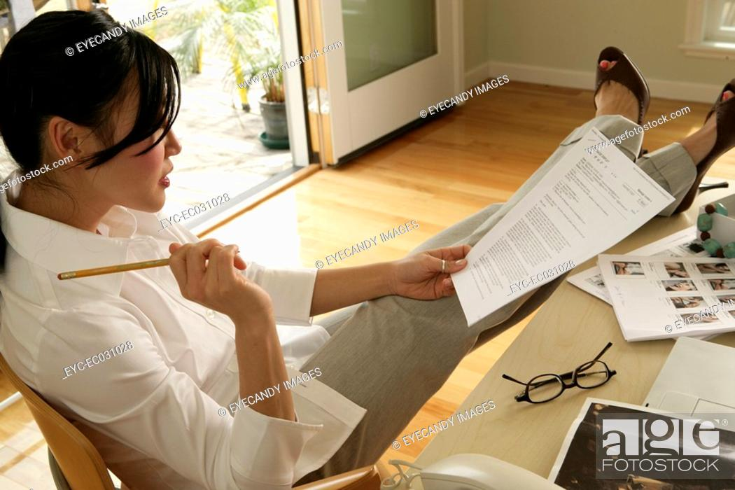 Stock Photo: Young woman sitting on chair reading paper, side view.