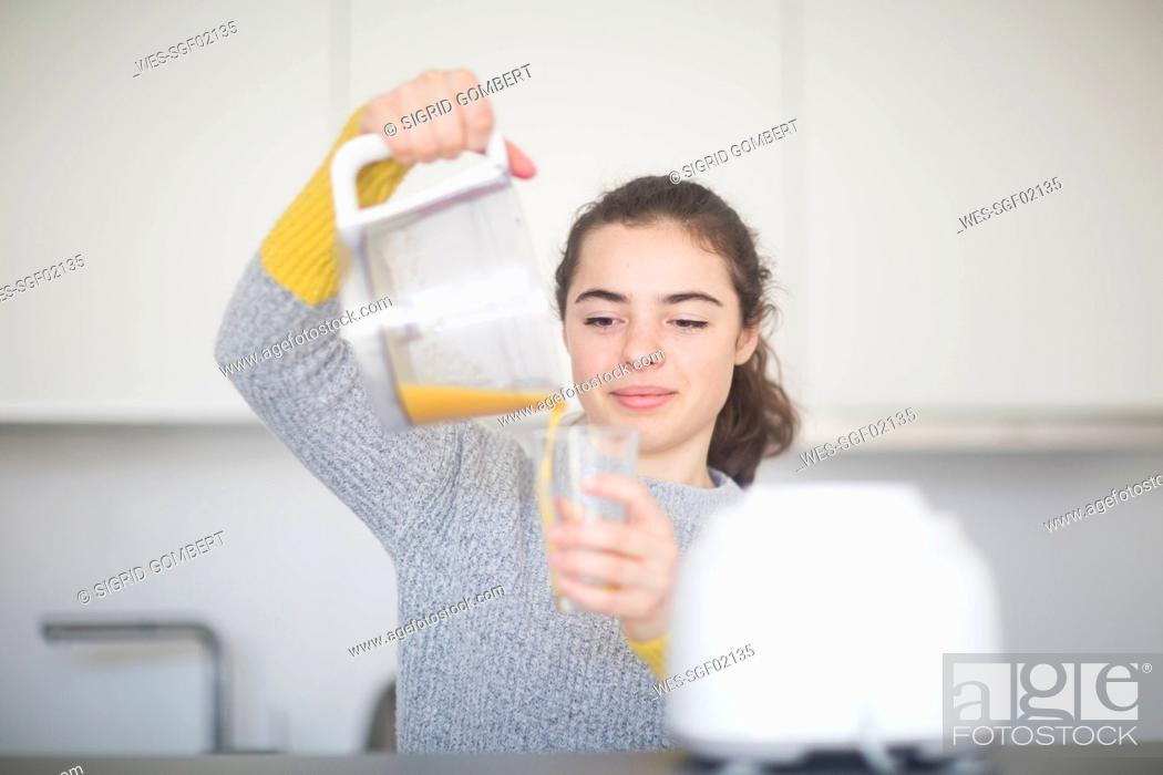 Stock Photo: Portrait of smiling woman pouring freshly squeezed orange juice into a glass in the kitchen.