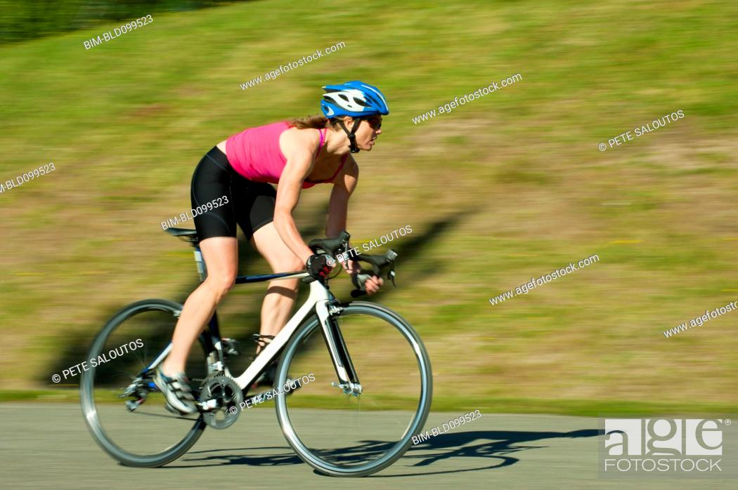 Stock Photo: Caucasian woman riding bicycle in park.