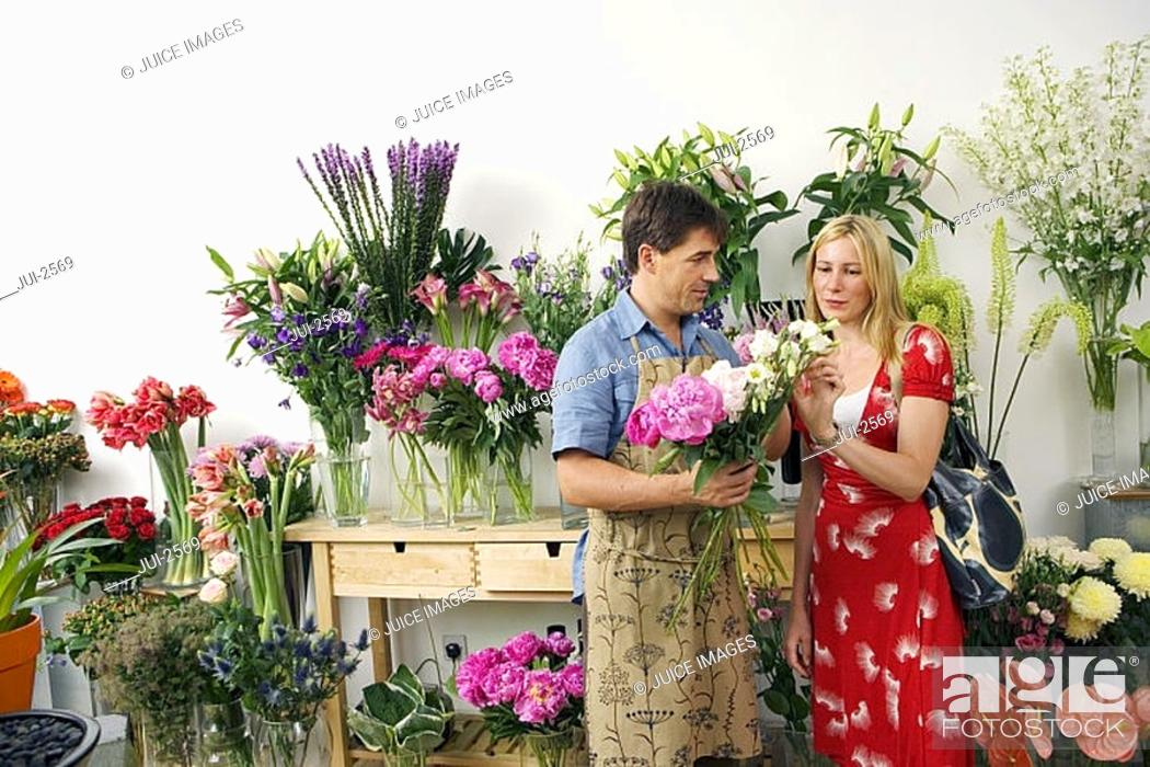 Stock Photo: Male florist serving woman beside display in flower shop, holding bunch of flowers, woman choosing.