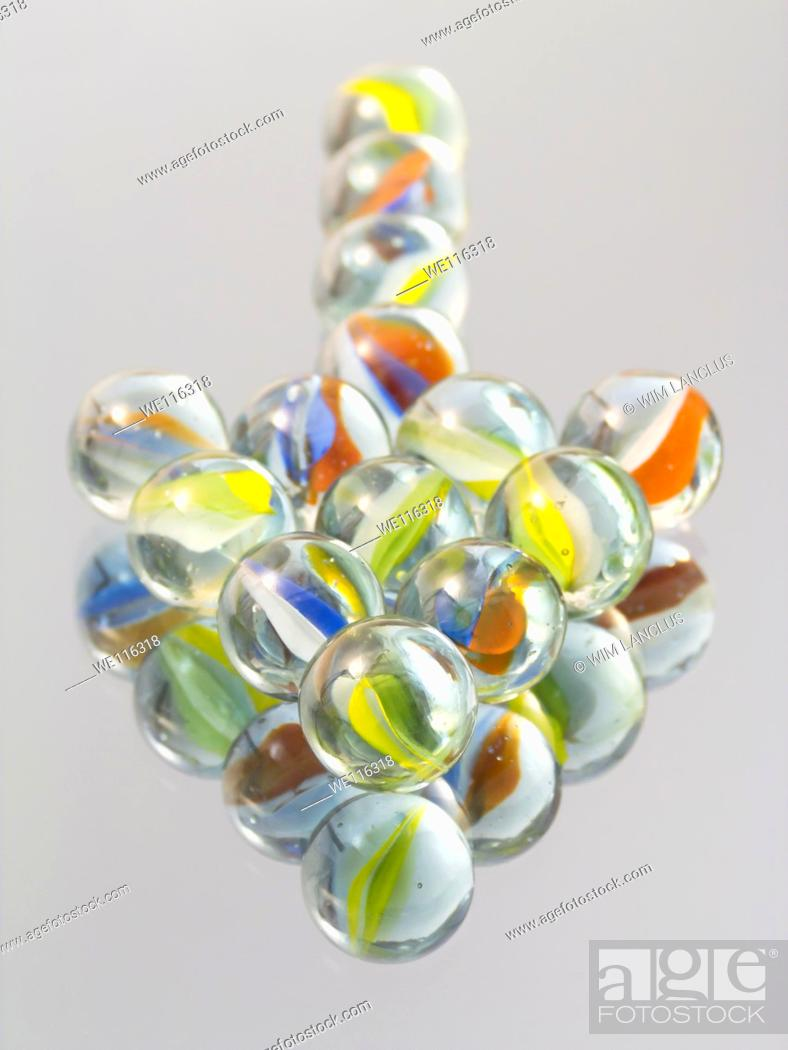 Stock Photo: Marbles shaped into arrow pointing at viewer on mirror.