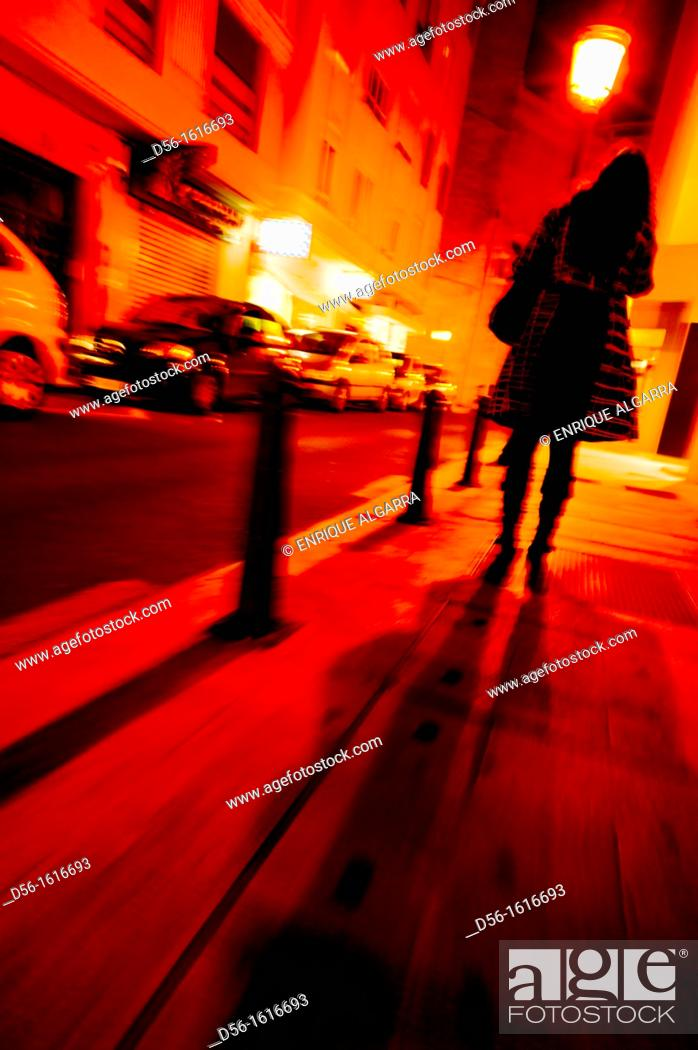 Stock Photo: woman walking at night, Valencia, Spain.