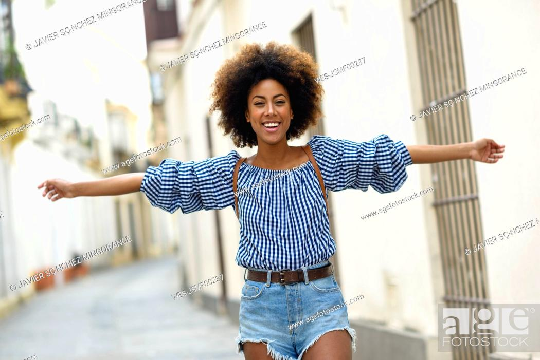 Imagen: Portrait of happy young woman with curly brown hair on the street.