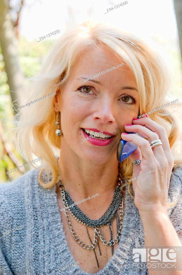 Stock Photo: Portrait of a 44 year old blond woman talking on a mobile phone, outdoors.