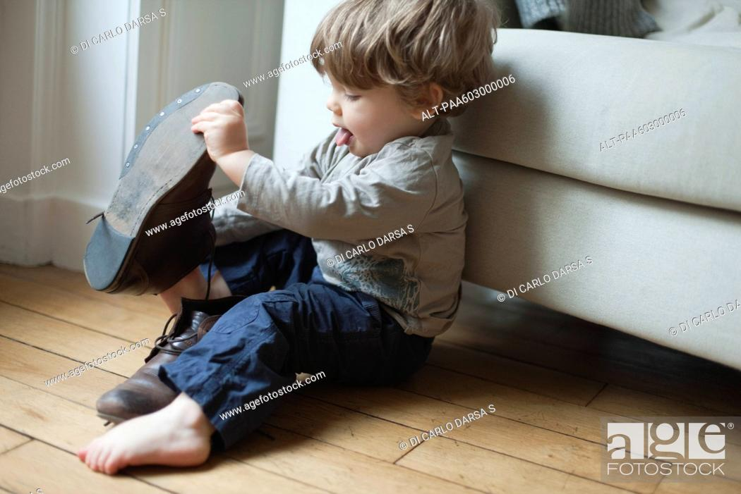 Stock Photo: Toddler boy playing with parent's shoes.