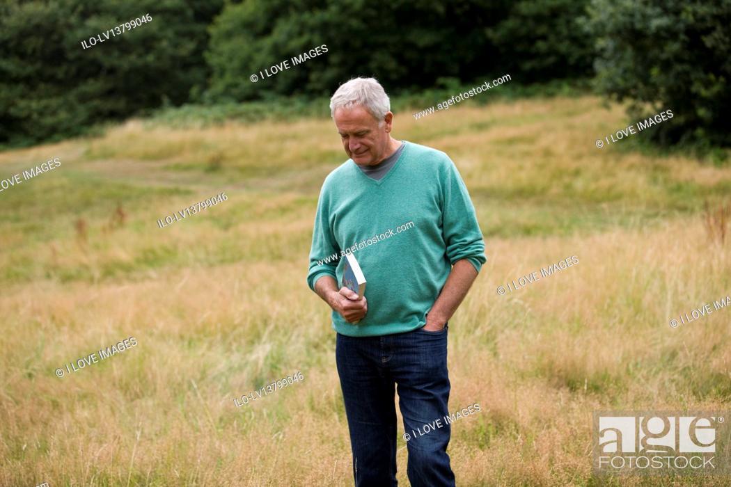 Imagen: A senior man standing in a field, holding a book.
