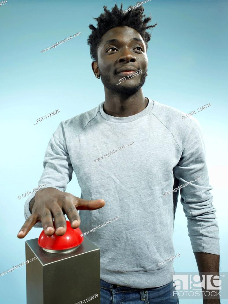 Stock Photo: A hip young man with his hand poised above a red game show buzzer.