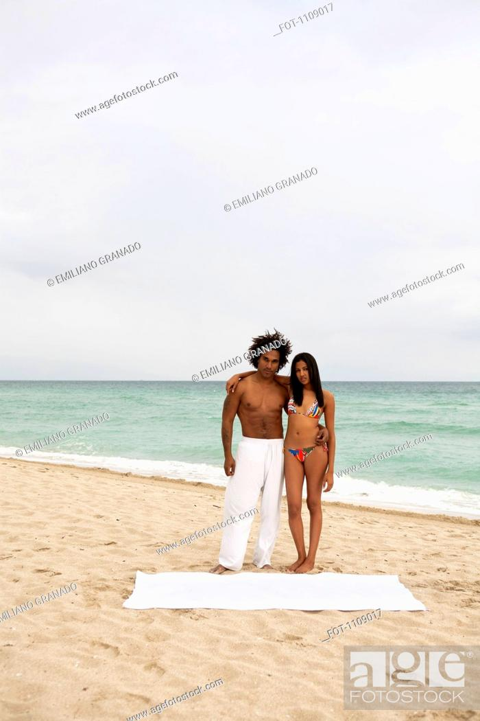 Stock Photo: An attractive young couple standing on a beach.
