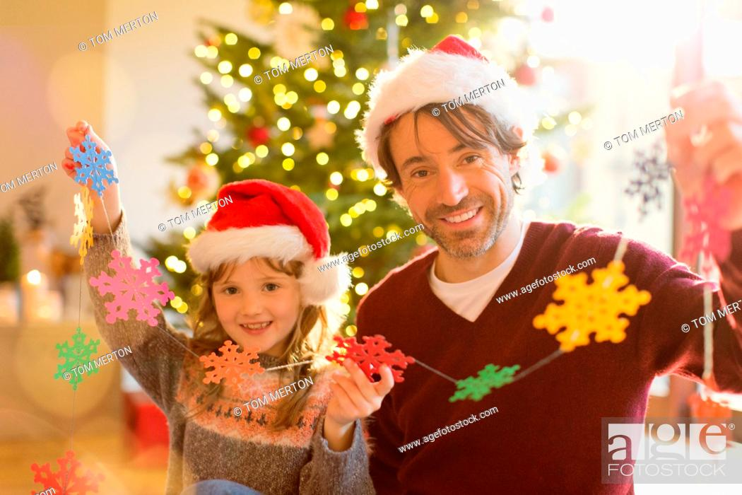 Stock Photo: Portrait smiling father and daughter in Santa hats holding string of paper snowflakes.
