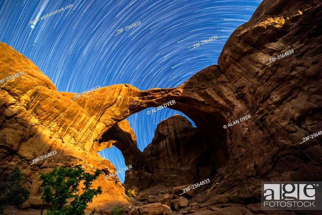 Stock Photo: Circumpolar star trails spinning behind Double Arch at Arches National Park, Utah, as the waning gibbous Moon lights the arches toward the end of the sequence.