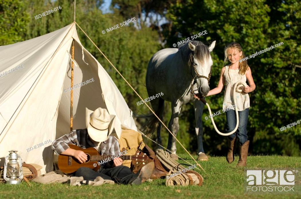 Stock Photo: A boy playing a guitar and a girl walking a horse.