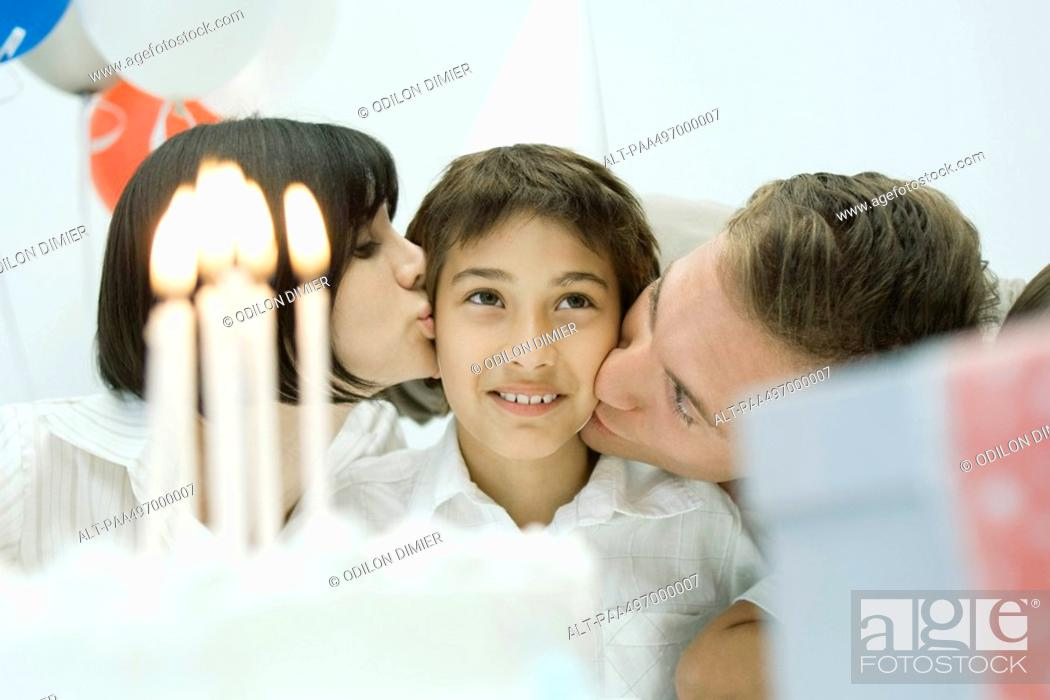 Stock Photo: Family behind birthday cake with lit candles, parents kissing boy on cheeks.
