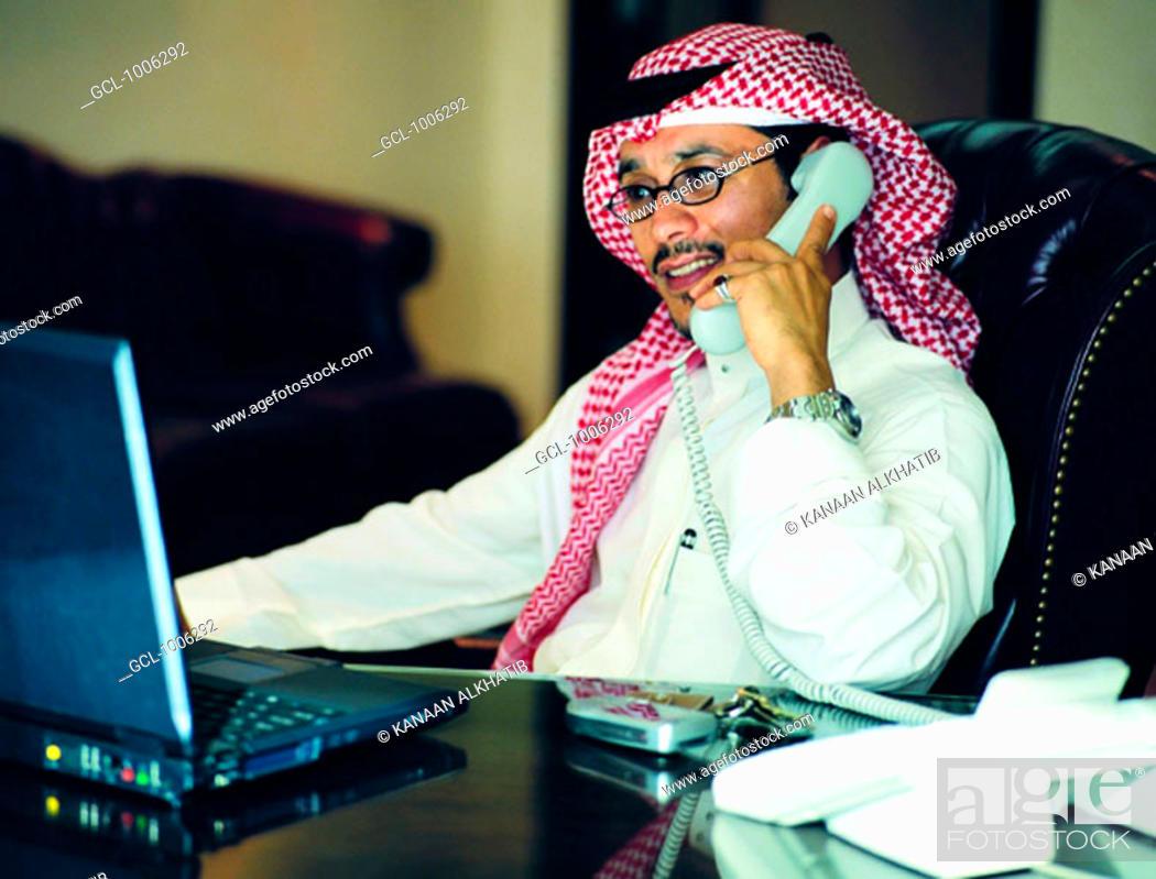 Stock Photo: Saudi businessman working on laptop and using telephone.