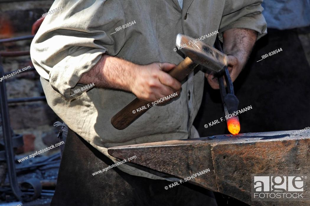 Smith in historical costume working glowing iron with his hammer