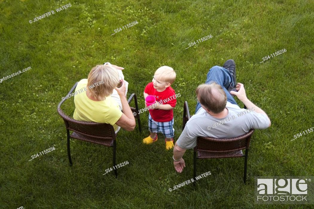 Stock Photo: A toddler smiling with his grandparents.
