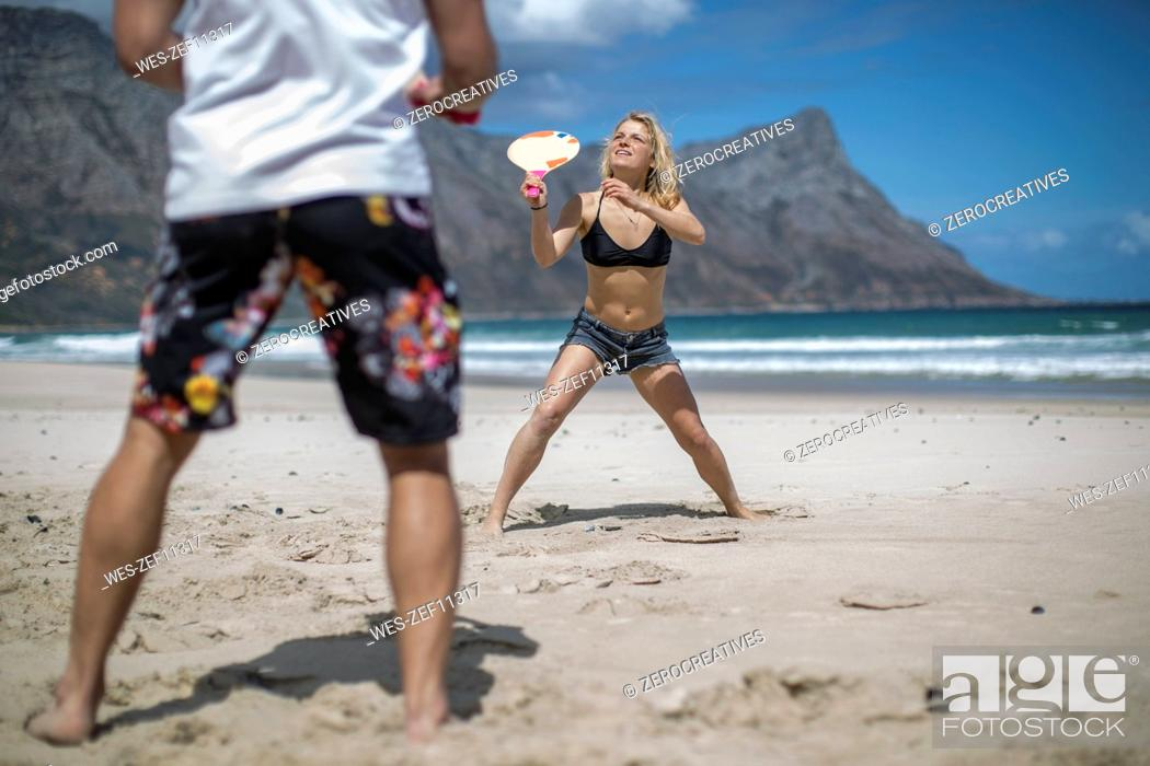 Stock Photo: Young couple playing beach paddles on the beach.