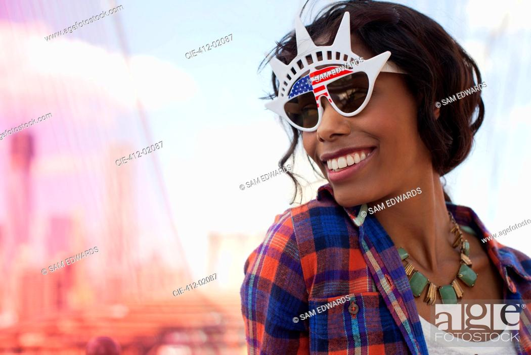 Stock Photo: Woman wearing novelty sunglasses on city street.