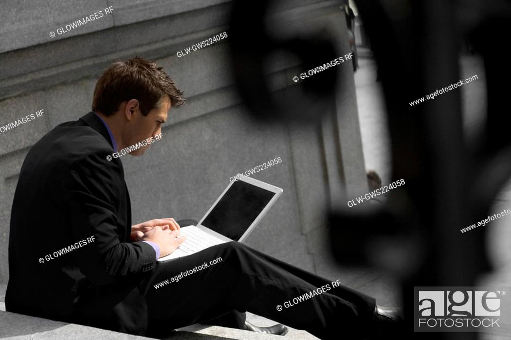 Stock Photo: Side profile of a businessman sitting on steps and using a laptop.